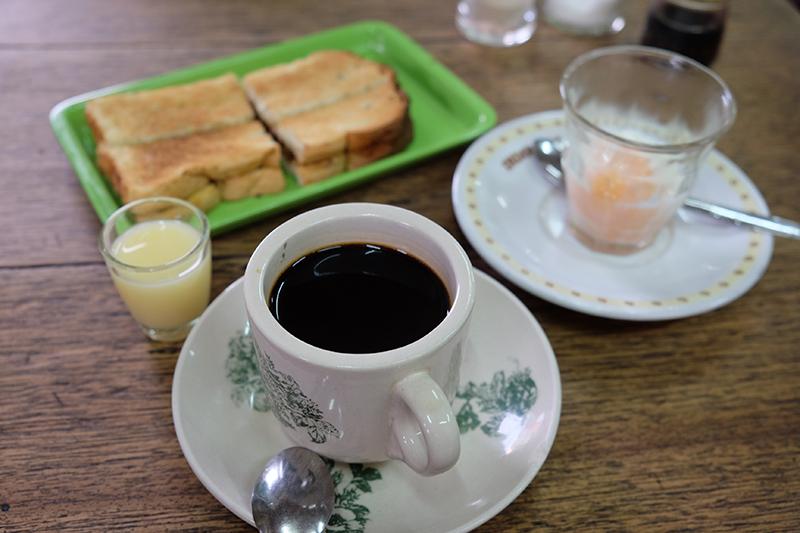 Sajian khas di Kedai Kopi Apek, ada kopi susu, roti bakar dan telor ayam kampung setengah matang.